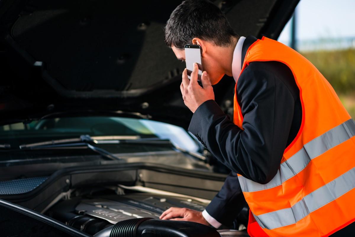 kierowca pochyla się w kamizelce odblaskowej nad maską auta z telefonem w dłoni